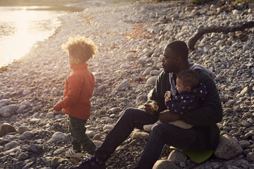 Father sitting with sons on rocks at beach