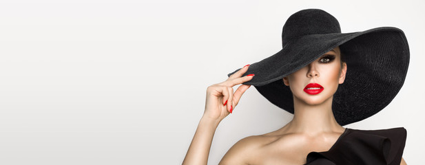 Portrait of an elegant woman in a hat and red lips on a white background Wall mural