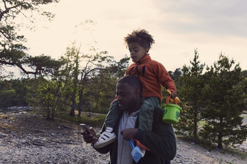 Father using mobile phone while carrying son on shoulders against sky