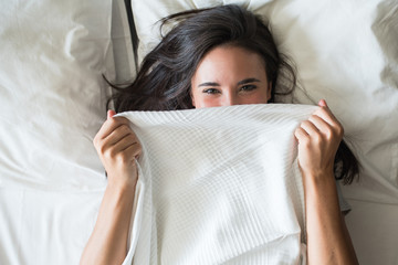 Woman covering face with blanket