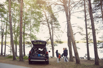 Family standing by car amidst trees during camping at beach