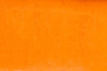 Vivid bright orange color facade wall as an empty rustic background texture space.