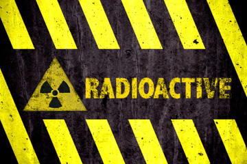 Radioactive (ionizing radiation) danger symbol and word with yellow and black stripes painted on a massive concrete wall with rustic texture background.