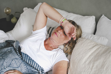 Senior woman suffering from cold lying on bed at home
