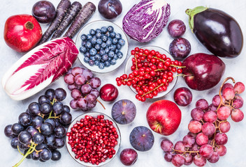 Red and purple fruits and vegetables, berries top view.