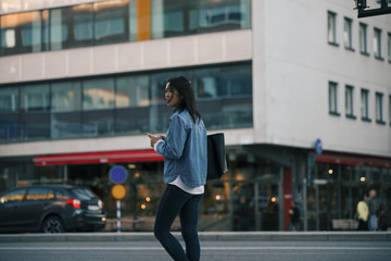 Teenage girl walking with smart phone against building in city