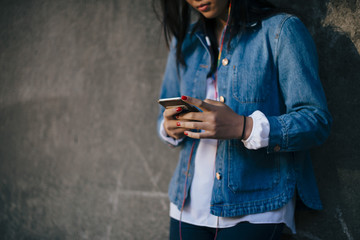 Midsection of teenage girl using mobile phone against wall