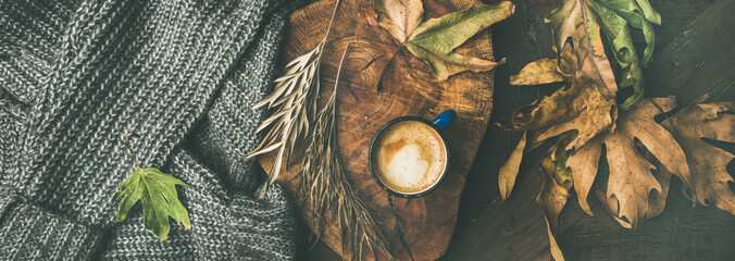 Autumn or Fall morning coffee concept. Flat-lay of knitted woolen grey sweater, wooden tray, mug of coffee and yellow fallen leaves over dark rustic wooden table background, top view, wide composition