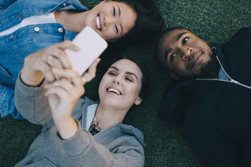 High angle view of smiling woman taking selfie with friends while lying on grass