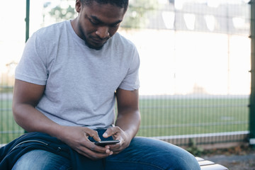 Young man using a smart phone while sitting on bench