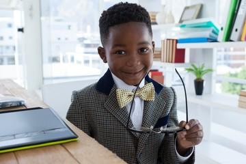 Obraz Portrait of smiling boy imitating as businessman holding - fototapety do salonu