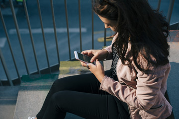 Young woman using a smart phones while sitting on steps