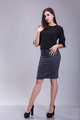 Full length portrait of a serious trendy woman in black dress standing on a gray background