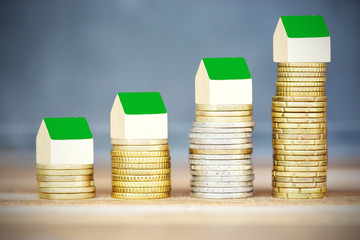 Rising cost of houses, real estate concept, with stack of coins and small wooden houses