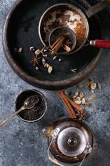 Vintage pot of traditional indian masala chai tea in stone tray with ingredients above. Cinnamon, cardamom, anise, sugar, black tea in glass teapot over dark texture background. Top view with space