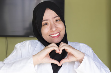 beautiful young  muslim doctor woman  showing heart shape with her hands