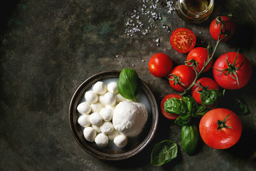 Tuinposter Buffel Ingredients for italian caprese salad. Mozzarella balls, buffalo in metal vintage plate, tomatoes, basil leaves, olive oil with vinegar over dark background. Top view with space. Rustic style