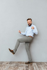 Full-length image of happy screaming bearded man in business clothes