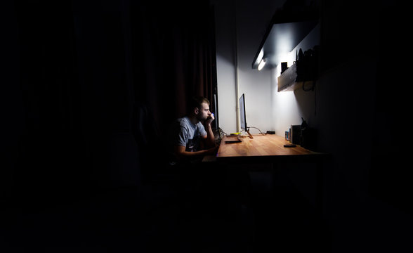 man works, resting at night at the computer in the room at home,  in the dark