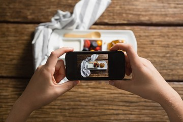 Hands taking photo of breakfast with mobile phone