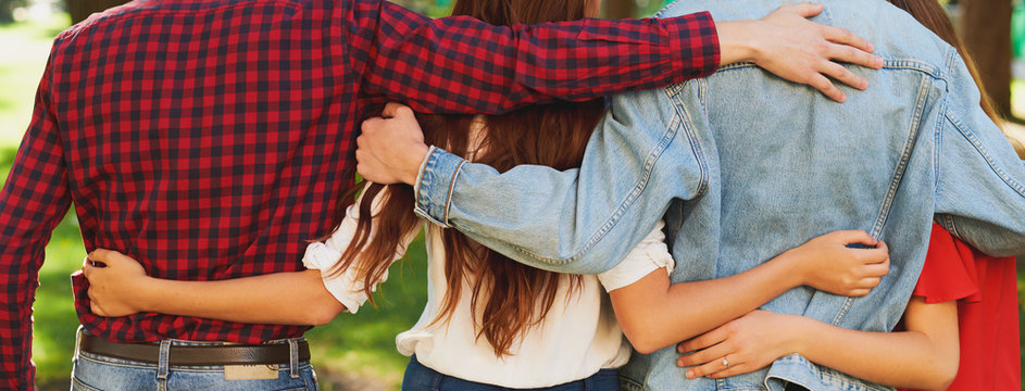 Best friends forever. Group of happy young unrecognizable man and woman hugging together and talking on city street from back. Happiness, leisure, friendship, teamwork, family travels concept