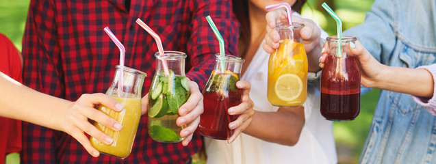 Healthy nutrition. Group of people drinking fresh juice detox on green nature background. Youth lifestyle, vegetarian diet to go, fitness food, successful weight loss concept