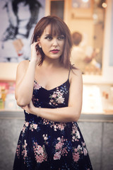beauty redhead girl in street wearing a flower dress