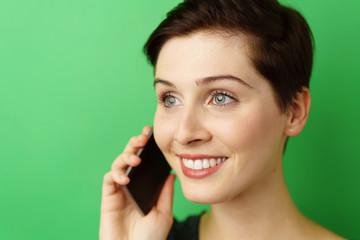 lächelnde frau telefoniert mit ihrem mobiltelefon