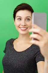lächelnde frau macht ein selfie mit ihrem smartphone