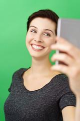 lachende frau fotografiert sich mit ihrem handy