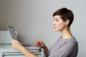 junge geschäftsfrau mit kurzen haaren schaut auf ihr notebook