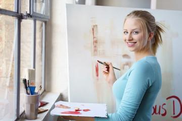 junge künstlerin malt in ihrem atelier
