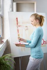 kreative junge frau malt in ihrem atelier