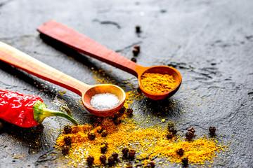 spices in wooden spoon on dark background