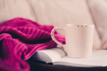 Cup of tea staying on open book with knitted sweater in bed. Good morning.