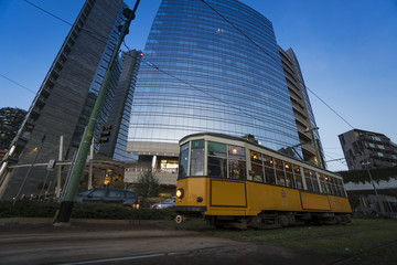 Old tram passes, at dusk, in front of new glass buildings in Milan, Italy.