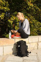 Blonde fitness female taking break from intense workout and listening to music.