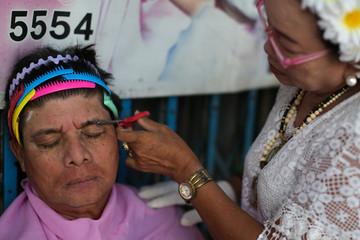 A man has his eyebrows cut at a market in Bangkok's Chinatown
