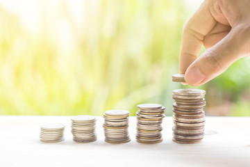 Closeup of hand put coins to stack of money with nature background-Business growing and saving...