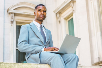 Way to success. Young African American College Student studying in New York, dressing formally in suit, tie, siting outside office building on campus, working on laptop computer, looking up, thinking