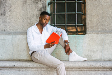Young African American College Student studying in New York, wearing white shirt, light gray pants, sneakers, wristwatch, sitting against vintage wall with window on street, reading red book..