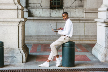 Young African American College Student studying New York, wearing white shirt, light gray pants, white sneakers, sitting on metal pillar on vintage street, working on laptop computer, looking away..