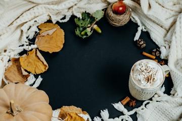 Cozy Autumn Composition. Pumpkin Latte, Cinnamon and plaid on a Black Background