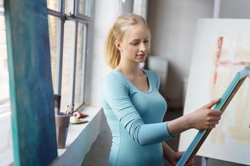 junge künstlerin mit bildern in ihrem atelier