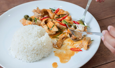 Red pork curry (Panang) with rice in white plate on wooden background, Thai food