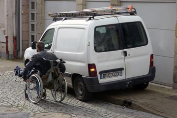 Personne en fauteuil roulant obligée de passer sur la route à cause d'une voiture mal garée
