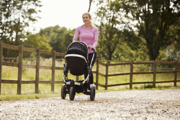 Mother Exercising By Running Whilst Pushing Baby Buggy
