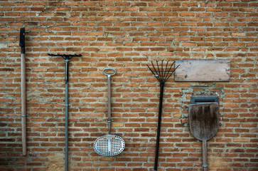 Farm and agriculture tools hanging on brick wall.
