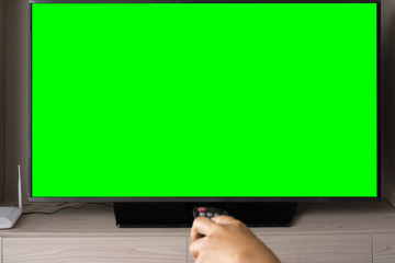 Green screen TV with defocused hand holding remote control