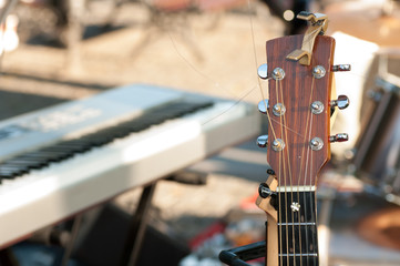 acoustic guitar fingerboard closeup background electric keyboard on the street before presentation